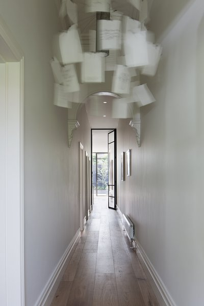 An Ingo Maurer Zettel'z 5 chandelier hangs in the entry hallway; sunlight from the home's expansive backyard is already visible on the white smoked oak floors.