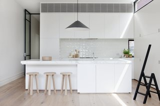 Black-rimmed steel clerestory windows add illumination in this diminutive white kitchen where black accents abound. A black Aggregato Saliscendi Suspension light, designed by Enzo Mari and Giancarlo Fassina for Artemide, accents against the white Calacatta marble countertops and MAP's oak Milky Stools.