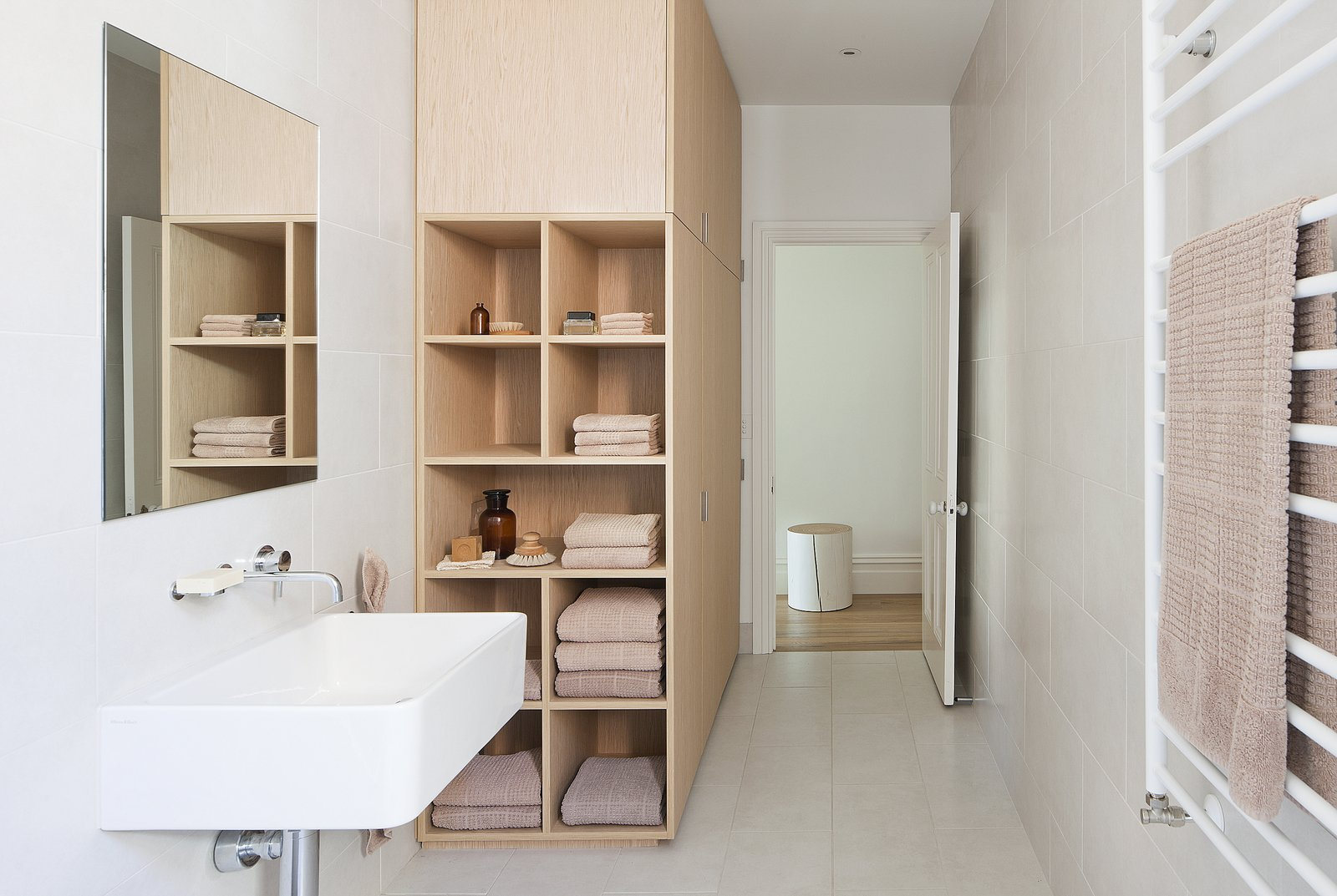 Storage Room, Wall Mount Sink, Ceramic Tile Wall, Ceramic Tile Floor, and Shelves Storage Type To stay within the budget, the designers decided to forgo natural stone in the bathrooms in lieu of simple vitrified tile. The bathroom isn't without its luxuries, however, as evidenced by the heated towel rail from Hydrotherm.  Best Photos from Seclusion