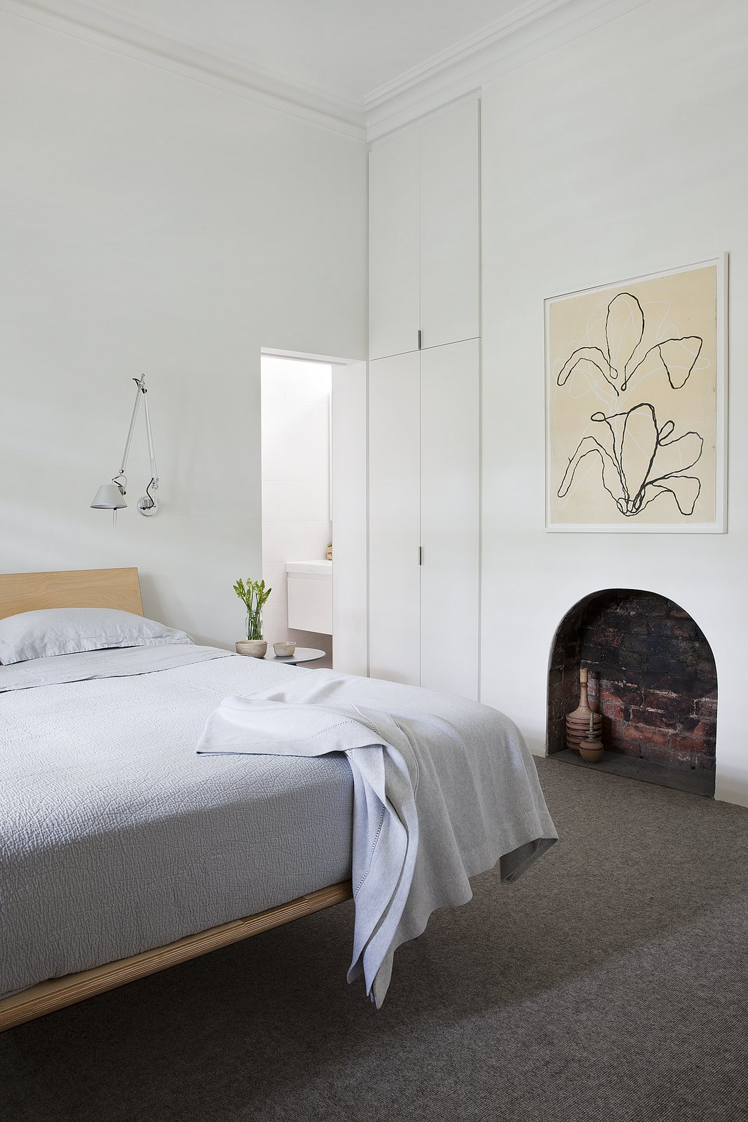 """""""[W]e didn't need a huge space for our clients to live in harmony, it just needed to be a well thought out space,"""" says the architects. A V Leg Bed by George Nelson is a classic addition to the bedroom, along with Tolomeo wall mounted luminaires from Artermide. The artwork is from David Band. Tagged: Bedroom, Bed, Wall Lighting, and Carpet Floor.  Our Favorite Bedrooms from Seclusion"""