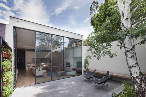 """The backyard features a vertical garden, called the """"picking wall"""" by the designers of Weller Landscapes, for its selection of kitchen herbs. In regards to the courtyard's wood and concrete finishes, the architects explain how """"[The] materials all had an honest raw quality about them, allowing them to age gracefully and acquire their own patina over time."""""""