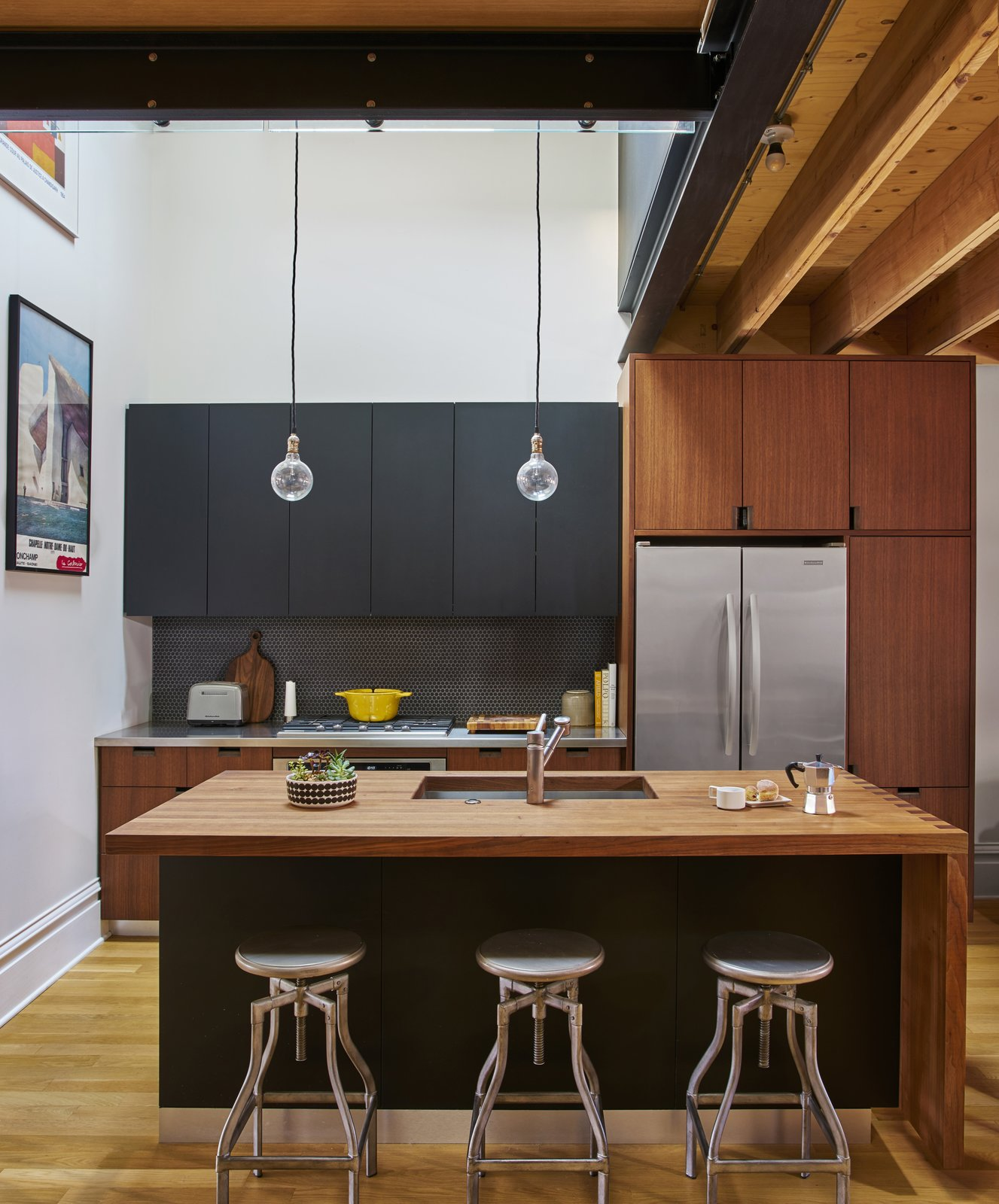 The kitchen features Schoolhouse Electric & Supply Co. pendant lights and Crate and Barrel stools. The woodblock island's leaf, at the far right, can lift upwards to expand the table when work or hosting demands it. The faucet is from KWC.  Photo 3 of 8 in A Chicago Renovation Taps Into its Attic to Almost Double its Square Footage