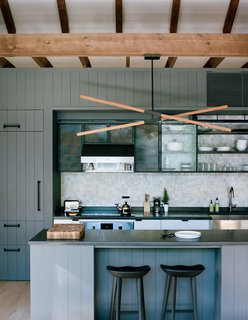 In New York about two hours north of New York City, architecture and interiors firm BarlisWedlick created an eclectic compound designed to suit a client with an idiosyncratic wish list. In the kitchen, a custom Stickbulb LED lamp hangs above a kitchen island topped by concrete from Get Real Surfaces. The cabinets and island feature a modern version of a traditional board and batten siding that are given an even more contemporary feel with the concrete countertop.