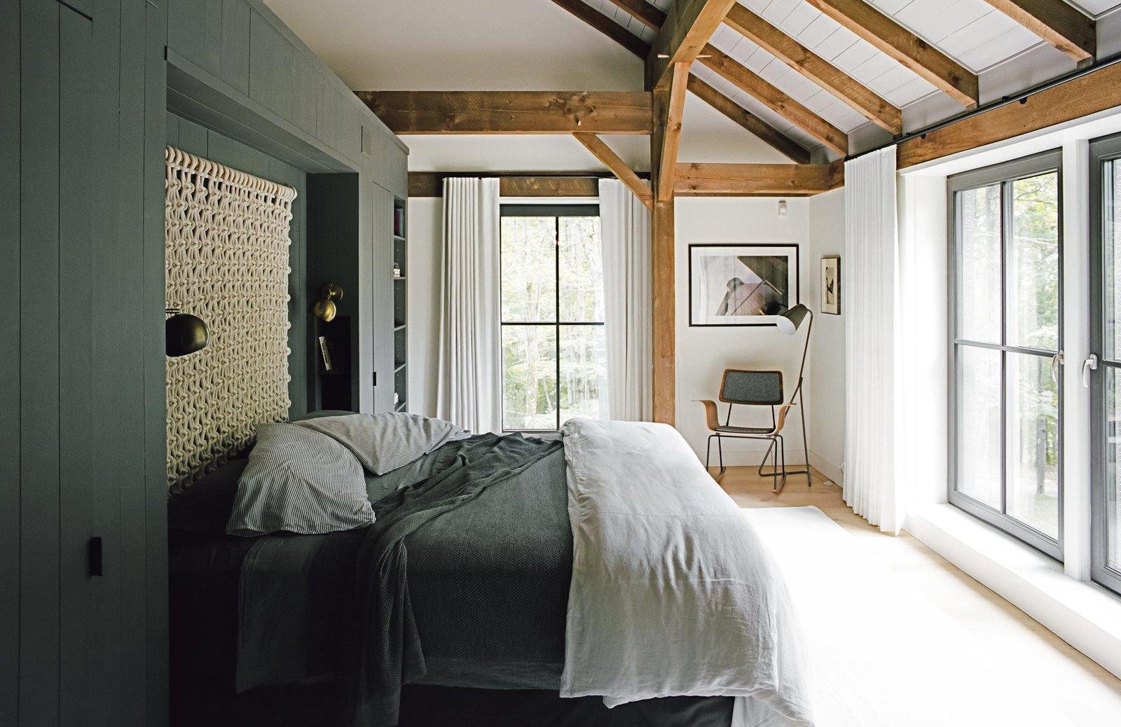 "Bedroom, Bed, Chair, Lamps, and Light Hardwood Floor The bedding is intentionally simple, without layers of unnecessary pillows, and the ""non-headboard headboard,"" as Santos describes it, is a loose macramé wall hanging by Sally England. The built-in storage wall that defines the space is painted Kendall Charcoal by Benjamin Moore in a matte finish—a shade used on millwork throughout the house. The Isaac brass sconces are from Schoolhouse Electric, and the floor lamp is from Crate & Barrel. The rocker was custom made by Onefortythree in Las Vegas.  Photo 4 of 13 in A Passive House and ""Sauna Tower"" Join a 19th-Century Barn in the Hudson Valley"