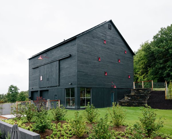 Two hours north of New York City, an unusual barn emerges from a hill just off a country road. Its black siding and bright-red window frames hint at the imaginative playground inside. This space, with its rope-railed catwalk and indoor tent, is just one element of the multifaceted getaway architecture and design firm BarlisWedlick Architects designed for fund manager Ian Hague.