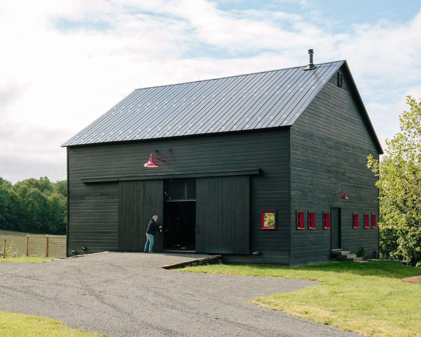 "Exterior, House Building Type, Barn Building Type, Wood Siding Material, Gable RoofLine, and Metal Roof Material Using technology to design a home as energy-efficient as possible was a priority for Hague, both from a financial and philosophical standpoint. Along with Passive House certification for the main house, a solar array on the roof of the barn keeps energy use near zero. In fact, the entire property was Net Zero before the addition of the pool, and it may soon generate an energy surplus with the addition of a second solar array at the main house.  Photo 10 of 13 in A Passive House and ""Sauna Tower"" Join a 19th-Century Barn in the Hudson Valley"