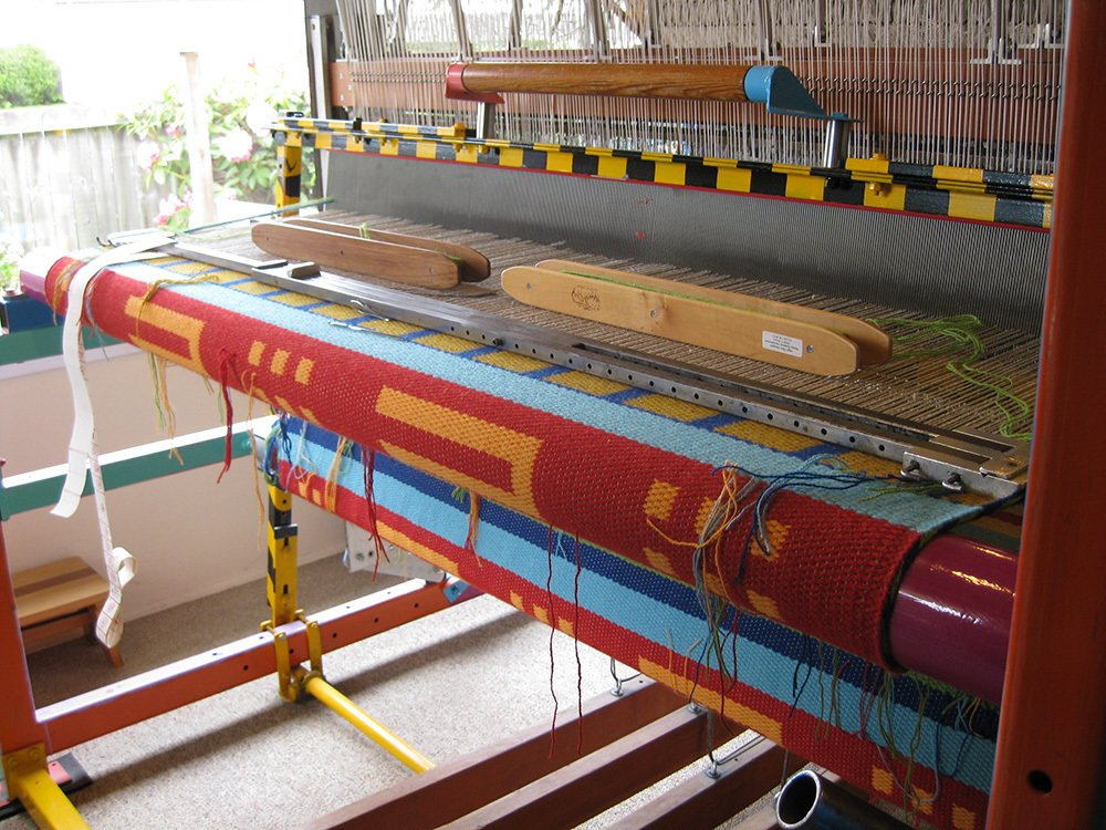 """What kind of loom do you use to make your rugs?  """"It was custom made for a technique called shaft-switching. I'm the second owner and long knew of the man who built it before the loom came on the market. When I bought it, the loom had been disassembled and on the previous owner's garage floor for three years. Once I got the loom to my studio I needed to figure out how it went together. There was no instruction manual...an engineer friend helped set it up. After that, I was up and running.""""  This American Maker Uses a Custom, Artist-Designed Loom to Create Geometric Textiles by Heather Corcoran"""
