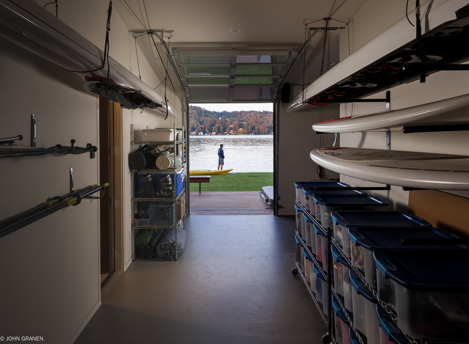 """They are a very active family, with rowing and basketball at the top of the list,"" Witt says. ""Other activities include water sports, volleyball, and entertaining—even in the winter months, which have short, usually damp days."" Witt created a garage deep enough to hang rowing shelves and enclosed it in a Wayne Dalton garage door.  Garage from A Richly Detailed Seattle Home Built Around a Family's Active Lifestyle"