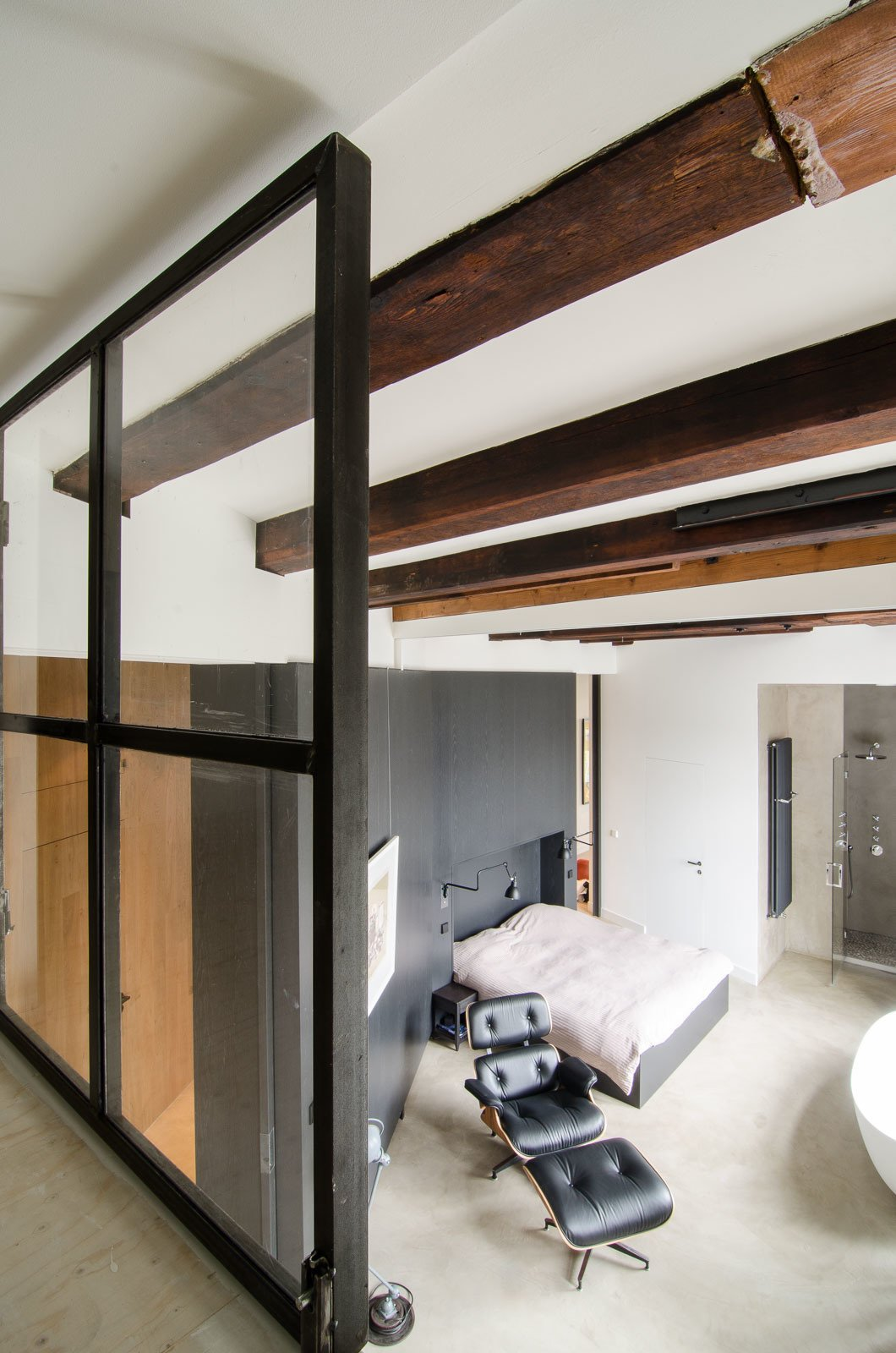 """The original beams, as seen from the loft, offer a warm and textural contrast to the sleek and modern finishes introduced during the renovation. """"There's a lot of nice patina to the very old beams; we definitely wanted to show that,"""" says van Hulzen.  Bloemgracht by Sarah Akkoush"""