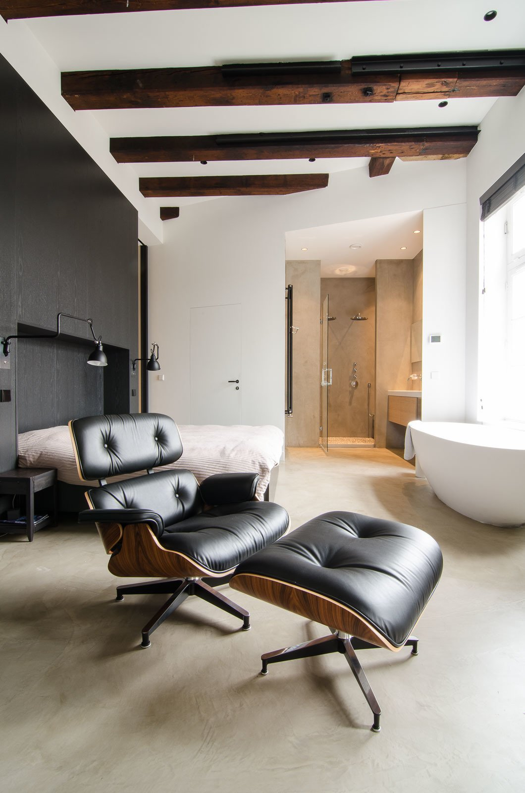 "When planning the renovation, the owner gave Standard Studio complete freedom to develop the design. In the unconventional bedroom, the bed sits against a black feature wall, with a prominent freestanding bathtub on the opposite side. In addition to the wood beams, all original windows from the old sugar refinery were preserved, to keep the ""soul"" of the building intact.  Loft from Bloemgracht"