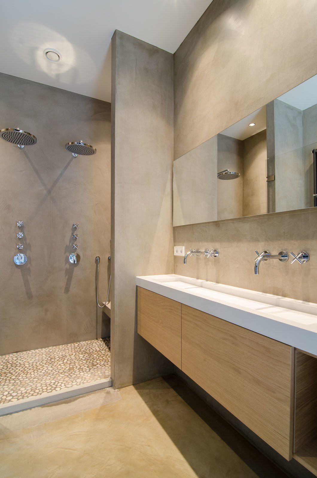 Adjacent to the bedroom, the bathroom features microcement-coated walls, along with a custom sink and vanity. Dornbracht Tara sink faucets and dual rainfall showerheads finish the space.  Bathroom from Bloemgracht