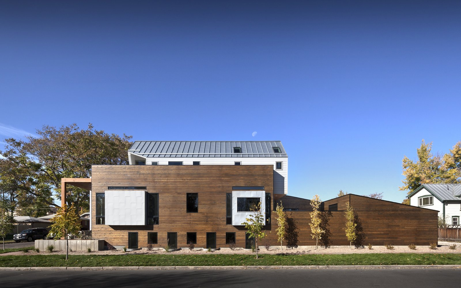 "Exterior, House Building Type, Wood Siding Material, Metal Siding Material, and Metal Roof Material ""Considering all of the foot traffic around their property, [the owners] made it very clear that they wanted to find a way to maintain as much privacy in the home as possible,"" architect Chad Mitchell says of this Denver home. ""Thus, the main floor of the home is elevated from the sidewalk by about six feet."" The exterior siding is red cedar with a custom Sherwin-Williams stain.  Modern Homes in Colorado by Luke Hopping from Highlands House"