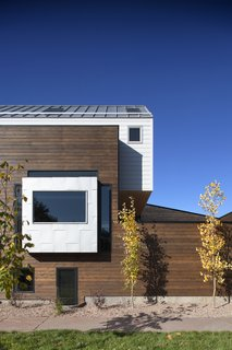 """Mitchell says that the red cedar """"provided a nice level of contrast from the white siding on top and helps to establish those two spaces as distinctly separate."""" The siding is from James Hardie."""