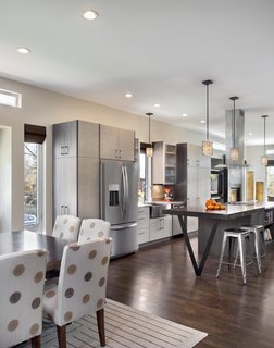 """Because the property is so narrow, we had to be strategic in laying out the plan,"" Mitchell says. ""Our goal was to create an open plan that spanned from exterior wall to exterior wall in order to make the home feel as large as possible."" Solid oak flooring fills the space and pendants from Kenroy Home illuminate the kitchen."