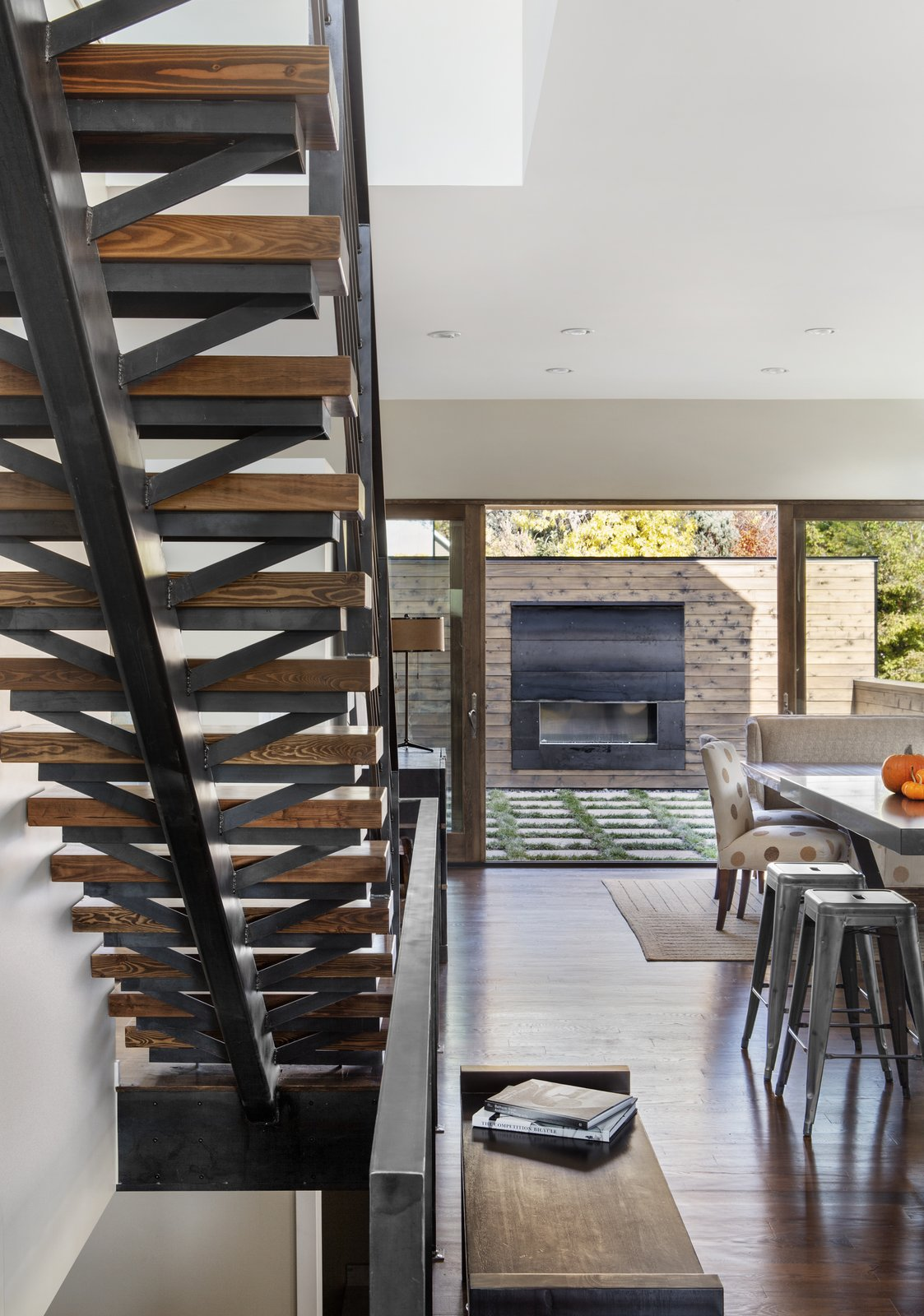 """Staircase, Wood Tread, and Metal Railing Mitchell wanted to detail the solid oak staircase with that same sense of openness, even though its materials are heavy. """"We used a lot of raw steel and wood on the interior of the home,"""" Mitchell said. """"This carries the authenticity of real materials from the building exterior to the building interior."""" A custom fireplace sits on the patio.  Photo 4 of 8 in A Couple's Denver Residence Makes Clever Use of a Narrow Plot from Highlands House"""