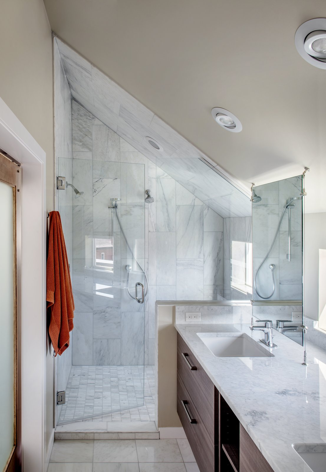 Bath Room, Enclosed Shower, Marble Wall, Recessed Lighting, Ceiling Lighting, Marble Counter, and Undermount Sink Carrara marble was used in the shower and on the countertops. The fixtures are from Hansgrohe.  Photo 6 of 8 in A Couple's Denver Residence Makes Clever Use of a Narrow Plot from Highlands House
