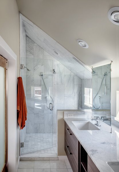 Carrara marble was used in the shower and on the countertops. The fixtures are from Hansgrohe.