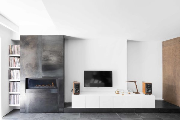 The communication between interior and exterior is unmistakable. The polished steel that surrounds the fireplace and the concrete floor's dark finish recall the home's exterior, while the contrasting stark white walls create a visual language as striking as the building's black facade.