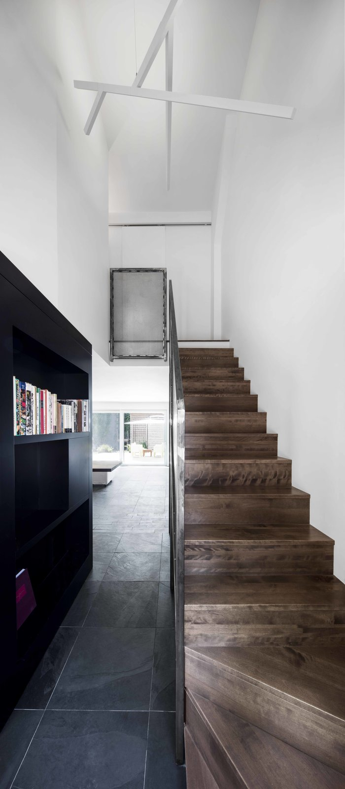 Staircase, Wood Tread, and Metal Railing The staircase's steel guardrail and the custom black bookshelf create a link between the kitchen, the living space, and the entryway.  Best Photos from A Monochromatic Renovation for a 19th-Century Montreal Home