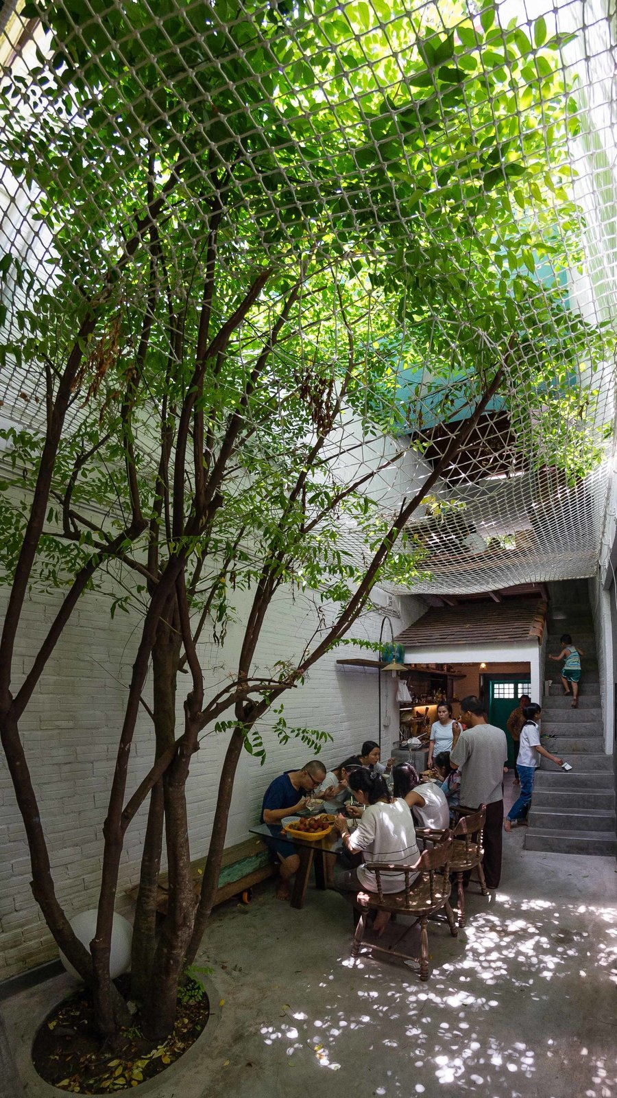 The family enjoys a shared meal in the ground floor alleyway, which serves as a gathering place, dining area, and playground. Native trees are planted on the ground floor as well as on balconies and in the steel frames, covering the home with plants and shifting the natural world inside.  Photo 5 of 10 in A Narrow Courtyard Joins a Unique Two-Family Home in Saigon