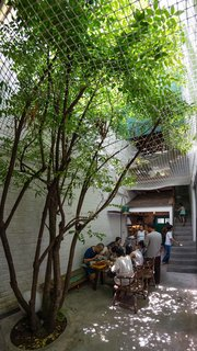 The family enjoys a shared meal in the ground floor alleyway, which serves as a gathering place, dining area, and playground. Native trees are planted on the ground floor as well as on balconies and in the steel frames, covering the home with plants and shifting the natural world inside.