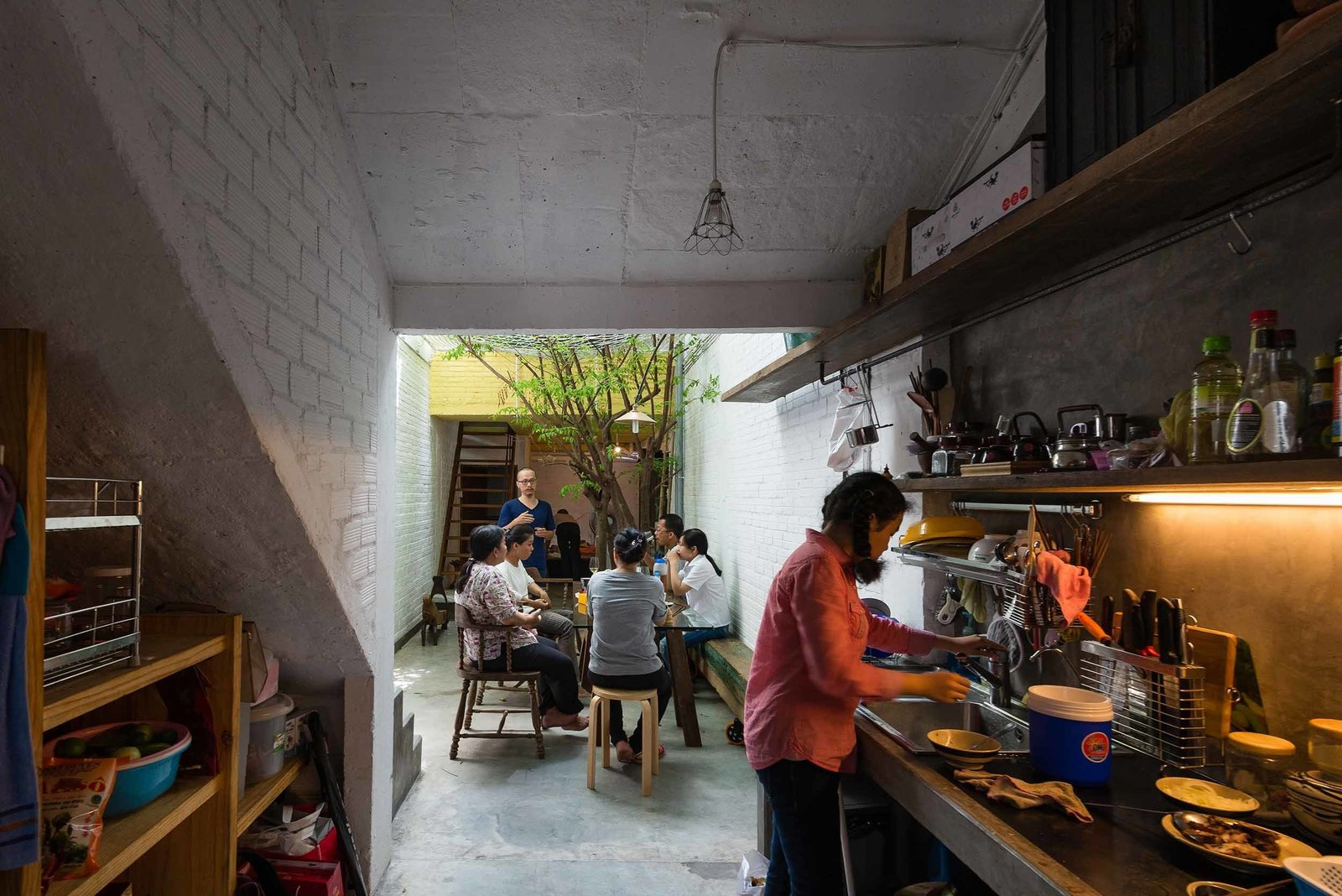 The alleyway extends into a full kitchen, where meals can be prepared right beside family gatherings. While the main frame of the home was built with the typical concrete, brick, and steel, the materials for the roof and floor tiles, as well as doors, windows, shelving and interior furnishings, were sourced primarily from demolished Saigon homes.  Kitchen from A Narrow Courtyard Joins a Unique Two-Family Home in Saigon