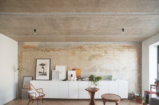 """Crosby Studios eventually found this rust-washed concrete wall underneath many layers of wallpaper. """"Nobody even thought to paint it,"""" explains Dmitry. """"The ceiling was polished until it was concrete, and then covered in laquer."""""""