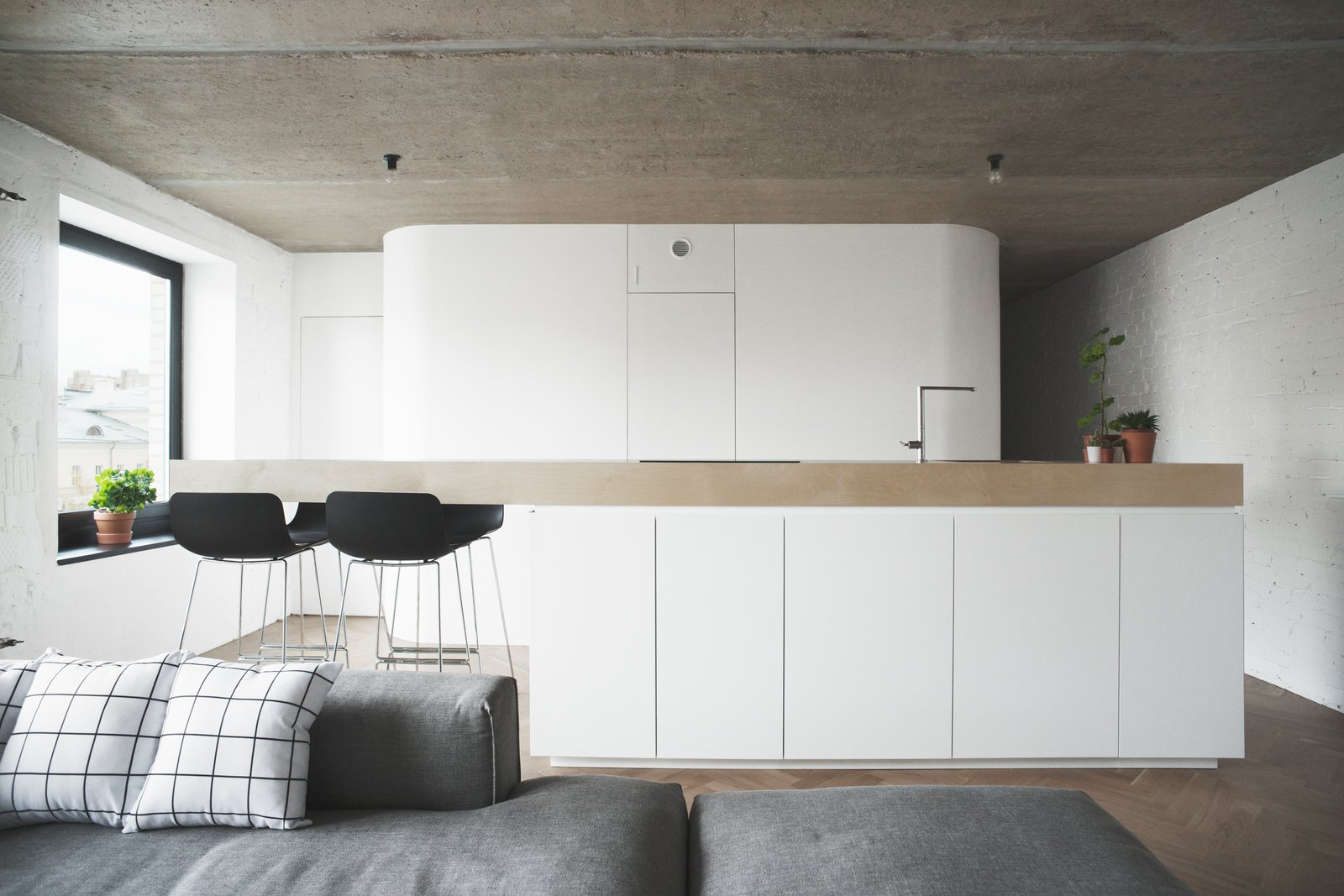 A gray Liam sofa is a smart solution for partitioning rooms while keeping an open plan in a small space. Black Enea Lottus stools also enable a joint entertainment/functional area.  Soviet Intelligentsia by Caroline Wallis