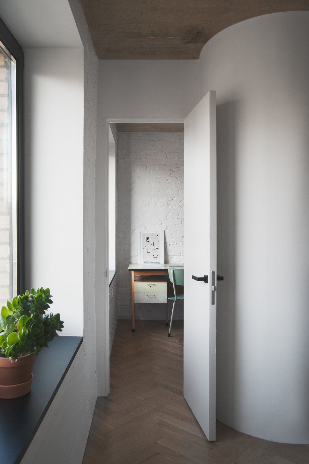 """To make the most out of a small footprint, Vorontsov experimented with some creative partitions. He explains how """"the partitions we built were straight, and then we rounded the corners slightly in the studio"""" to create a little extra room. """"We left the doors without architraves, and punctuated the detail with black doorknobs.""""  Soviet Intelligentsia by Caroline Wallis"""