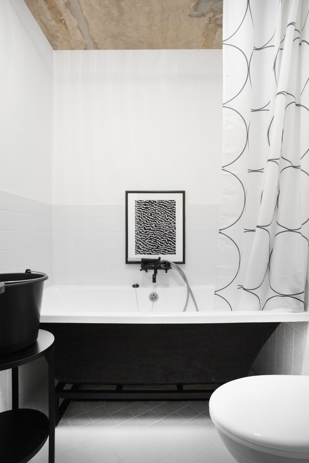 The approximately 4 inch by 4 inch white ceramic tile flooring is typical of Soviet-era bathrooms. Vorontsov sought to update the utilitarian style of the original bathroom with Kludi Bozz fixtures (which he painted black himself) and a graphic IKEA shower curtain.  Soviet Intelligentsia by Caroline Wallis