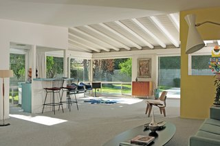 Its living room features an Eames LCW, Bertoia Barstools, and Eames Tandem Shell Seats.