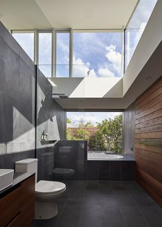 An Envy II Wall-Faced Suite toilet by Parisi sits in the home's sole bathroom and Caroma's Starlett 1850 Island Bath was installed next to the window.