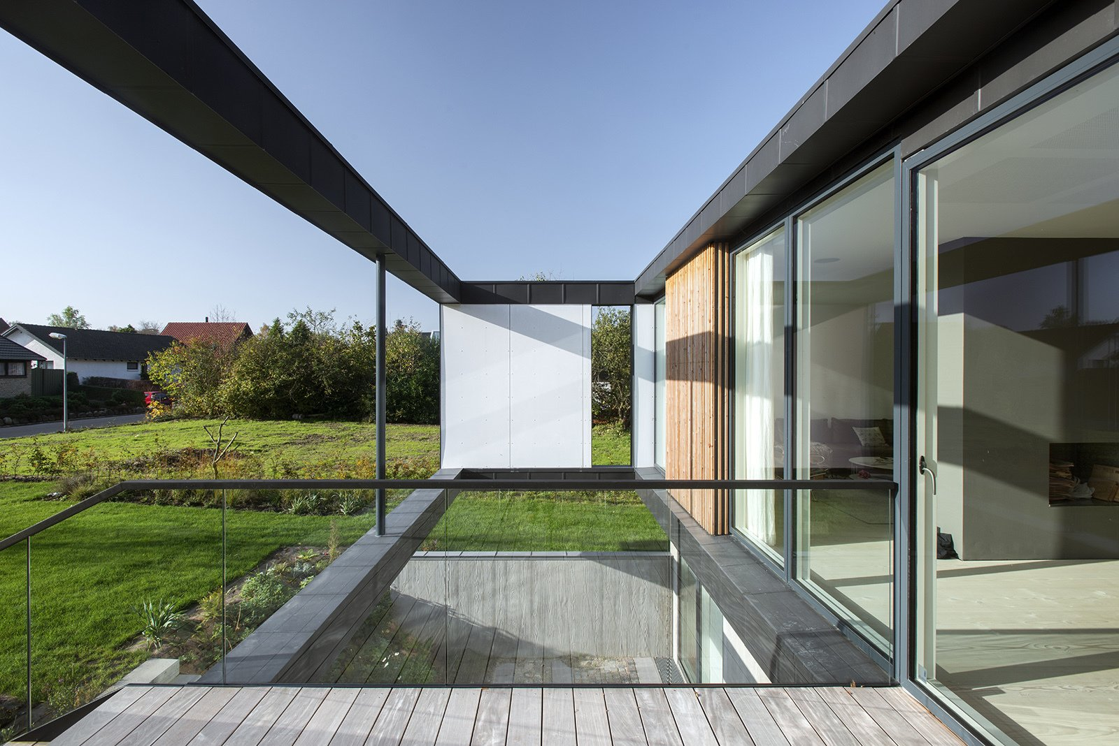 """Outdoor, Side Yard, Metal, Wood, Small, Shrubs, Decking, Grass, and Hanging Located in Aarhus, Denmark, Villa R is a minimalist, serene structure clad in zinc panels. """"The objective was to create a house that brings the forest inside through large glass panels—and create an ever-changing seasonal backdrop for the interior living spaces,"""" stated the architecture firm, C.F. Møller, of the 3,200-square-foot abode.  Outdoor Metal Side Yard Shrubs Photos from Villa R"""