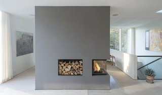 Scandinavian architecture firm C.F. Møller designed a serene, zinc-clad home in Aarhus, Denmark. On the interior, a large, three-sided fireplace incorporated into a floating wall helps connect two spaces and warm up the home, and the wall also incorporates a purpose-designed niche filled with firewood for easy re-stoking.