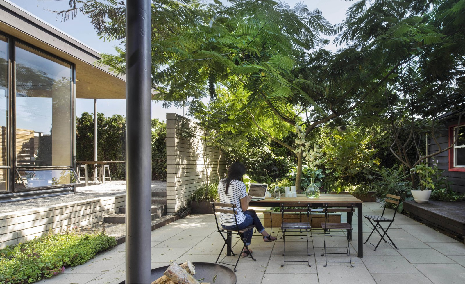 """Outdoor The courtyard is sunken because of the existing grade. The Albezia shade tree was planted when the outdoor area was still scrap yard, an """"act of hope and faith in the future,"""" says Wittman.  Search """"landscapes--trees"""" from A Blissful Retreat Replaces a Scrap-Filled Yard in Seattle"""
