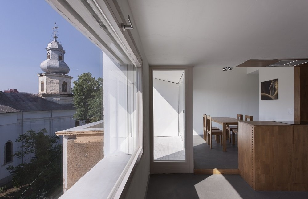 The main issue Lucerne-based architect Andreas Heierle faced during this attic renovation in Bucharest, Romania, was bringing natural light into the cloistered, closed-off rooms. His client, a bachelor in his 30s, wanted a floorplan that was flexible and open, a radical departure from the cramped, dark upper levels normally found in these types of apartment buildings. Heierle installed large windows, which flood the space with sunlight and provide a view of the church across the street.  Minimal Romanian Attic Renovation Complete with an Epic Bathtub by Patrick Sisson
