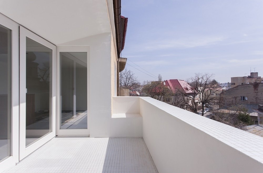 A different perspective of the terrace shows where the wall was knocked down to provide more outdoor space. As the balcony connects with the wall, a small seat was cut from a gap between two planes.  Minimal Romanian Attic Renovation Complete with an Epic Bathtub by Patrick Sisson