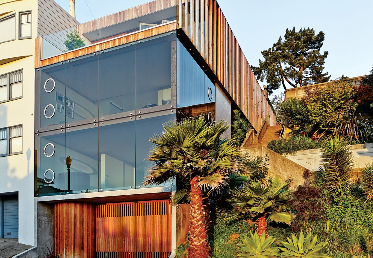 Exterior, House Building Type, Glass Siding Material, Flat RoofLine, Tile Roof Material, and Wood Siding Material For a San Francisco couple living on a hill overlooking the Mission District in San Francisco, glass walls were a must. Indoor louvers allow the residents to frame their view of the city, much like the aperture on a camera.  These Modern Glass Homes Shatter Conventions by Luke Hopping