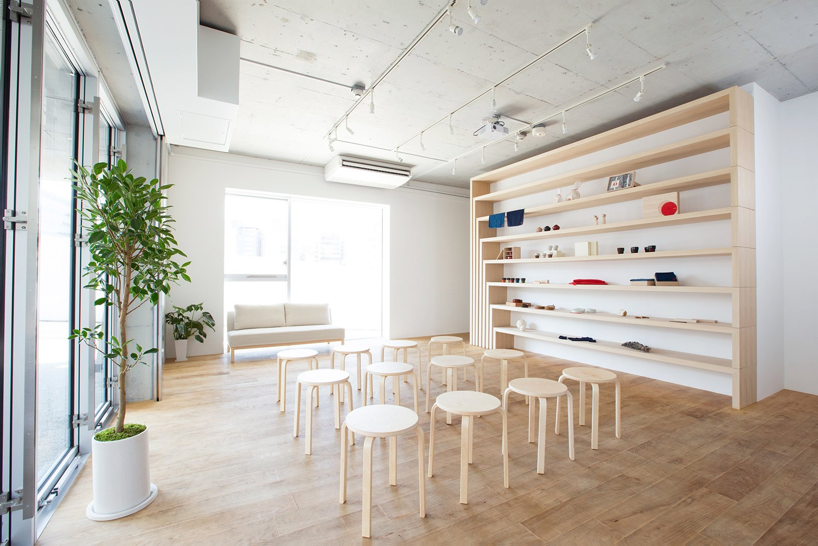 "When Aeru hosts workshops and events, the shelf rotates flat into the wall to accommodate seating. ""The cabinet changes form according to the occasion—it can be used to display products, or it can be used as a desk and bench,"" states the firm in its description of the concept. ""Thus, it allows one to use the shop space freely and flexibly. With this cabinet at its core, this shop reflects the fascination of Japanese craftsmanship.""  Shelves from A Space-Saving, Flexible Retail Design in Japan"