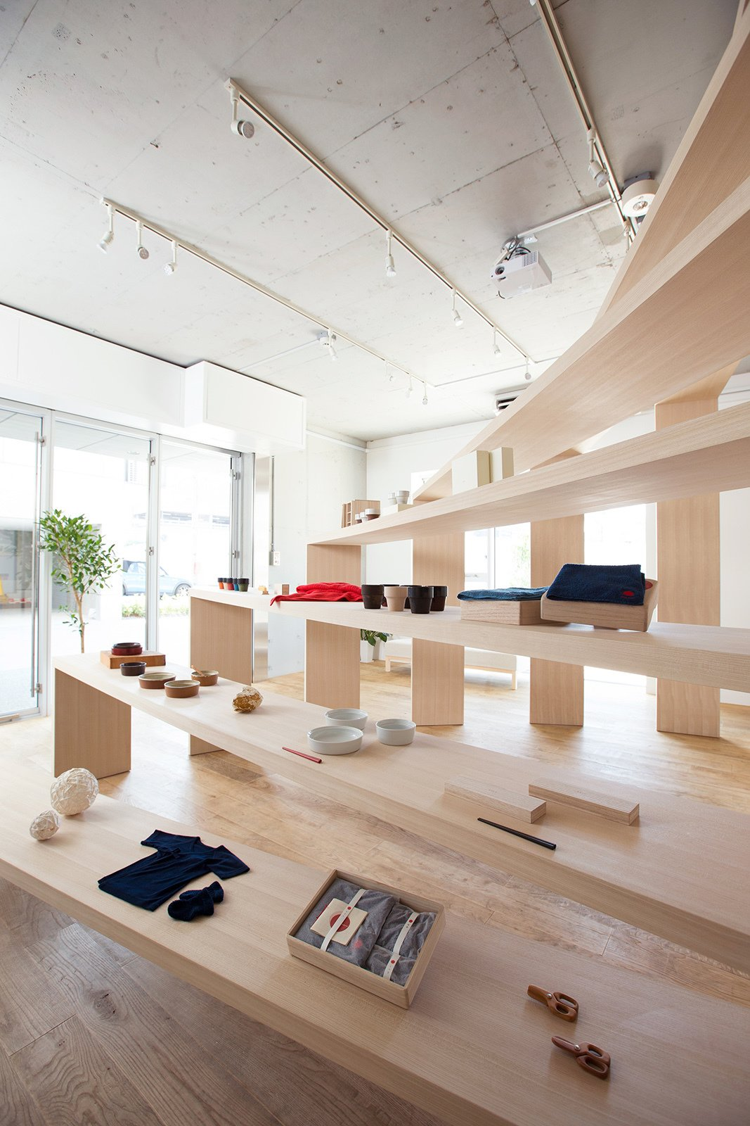 Nosigner used castor aralia wood for the design and comissioned a carpenter in Yokohama who specialized in large-scale furniture to build the shelf.  Bravo TV's Favorites from A Space-Saving, Flexible Retail Design in Japan