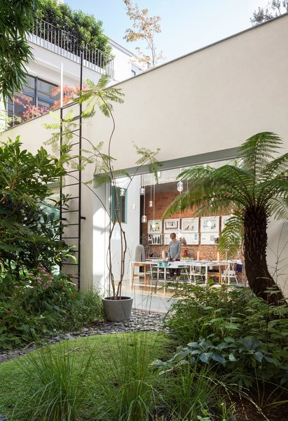 An artist and an architect built their home, studios, and an exhibition space inside a lushly landscaped Antwerp warehouse.