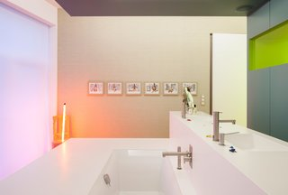 Installed by a local vendor, the Corian sinks and bath combine to form a freestanding island in the upstairs bathroom, outfitted with fixtures by Ritmonio. A series of artworks by Tim, including a sculpture that emits a soft glow, accent the pristine space.