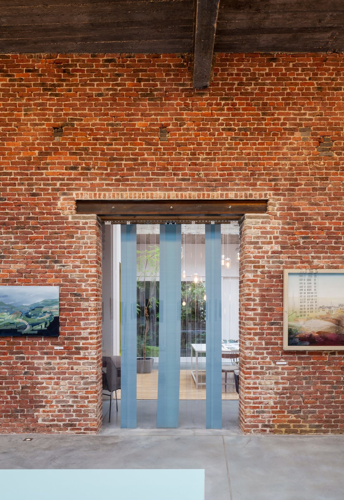 Exterior and Brick Siding Material With 5,000 square feet on the ground floor, the structure boasts two capacious exhibition spaces, which the couple use to show their own work, as well as rent out to others for private events.  Photo 10 of 12 in A Creative Dreamworld Complete With Neon Rooms and a Tropical Garden