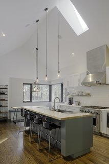 """""""Knowing that the kitchen would be where the family would spend most of their time, it was designed to have a variety of seating and really good views to the beautiful forest and field outside,"""" says Lewis. IKEA bar stools line up against white quartz countertops, and lighting by Schoolhouse Electric & Supply Co. shines overhead."""