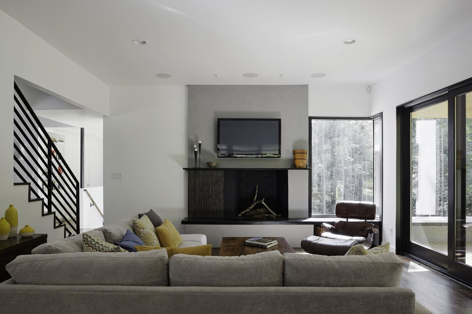 """Living Room, Chair, Standard Layout Fireplace, and Sofa """"We had to take into consideration that this young family was going to be living on a viable farm,"""" says interior designer Kris Ozburn of Second Mile Design. """"So, selecting furniture that was practical but had good design was a priority."""" Ozburn chose pieces like the sectional sofa from Precedent that felt timeless and modern.  The Farmhouse by Kelly Dawson"""