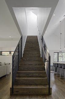 Stained oak flooring was used throughout the home's ground level, and continues up the main stairwell. Painted steel was used for the guardrails.