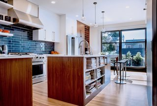 A first priority for the kitchen was sunlight: to maximize exposure, Mitchell Holladay Architects demolished as many walls as possible without compromising the home's structural integrity. LEM Piston stools by Shin and Tomoko Azumi from Design Within Reach flank a custom walnut kitchen island; sculptural hand-blown glass pendants from John Pomp Studios hang overhead.