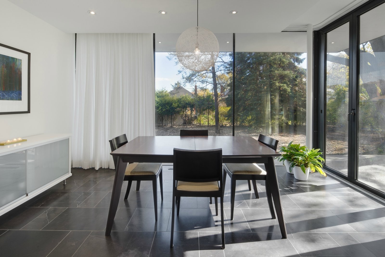 A table and accompanying chairs by EQ3 sit under a Moooi light fixture in the dining room, a room that was added to the original structure. Glass doors from NanaWall allow for the patio and dining area to become one cohesive space in the warmer months.  Art Moderne by Kelly Dawson