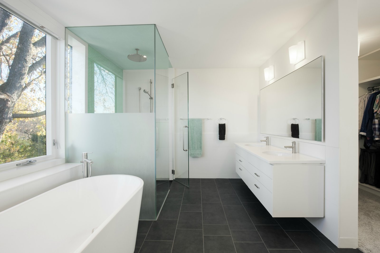 A Rubi bathtub by Ramacieri Soligo was installed beside a shower with Aquabrass finishes. Stone Tile International supplied the Amore porcelain tiles, in graphite black, that spread across the floor.  Art Moderne by Kelly Dawson