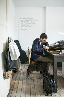 Verheyden works at his desk in the home office; over-flow projects are tackled in the workshop adjacent to the house, which is covered in black wood.